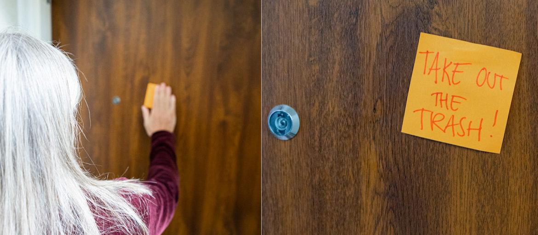 En kvinna sätter en lapp på en dörr där det står ta ut soporna