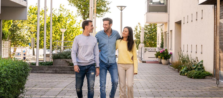 Tre ungdomar som går på en gata och pratar