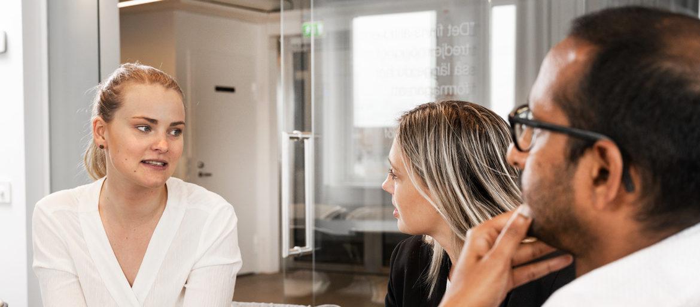 Två kvinnor och en man sitter vid ett bord och pratar
