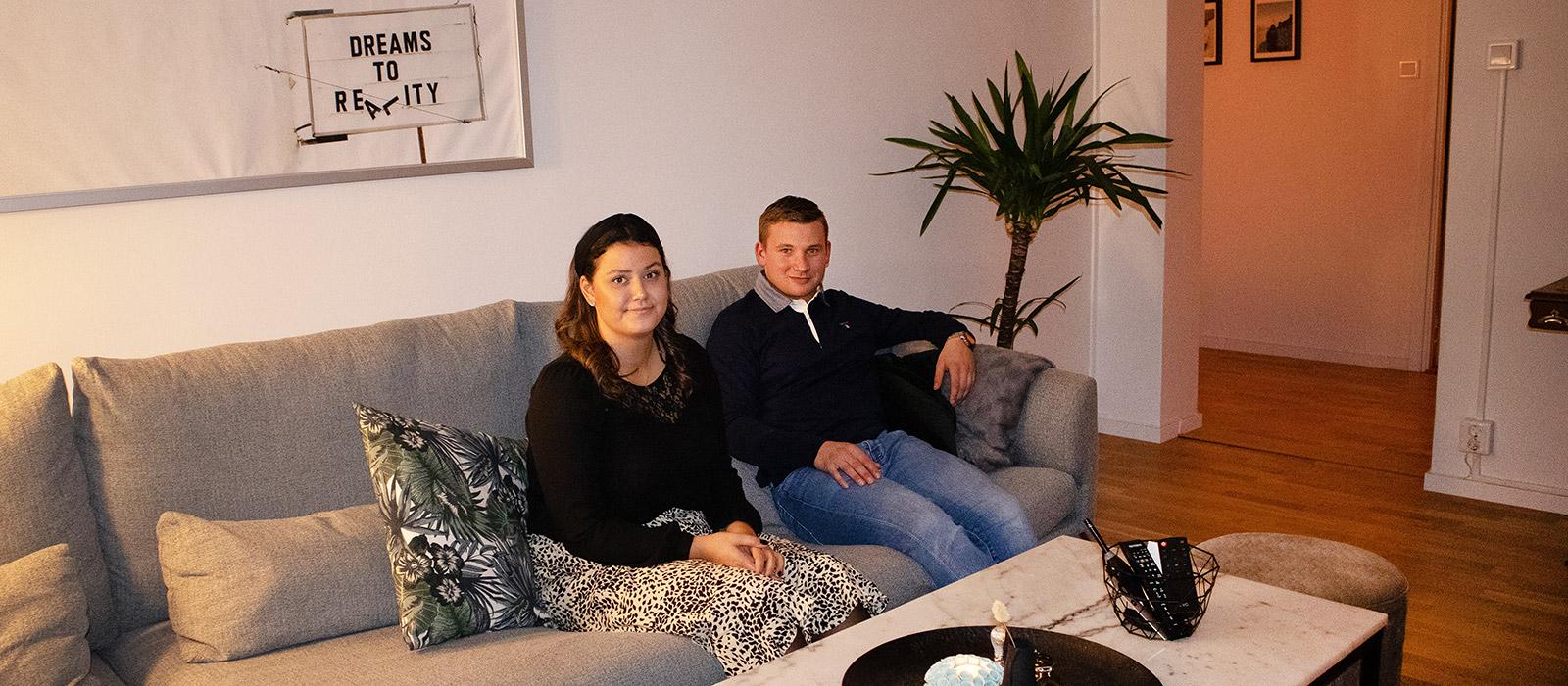 Ett par sitter i sin soffa i vardagsrummet