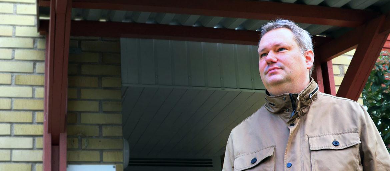 En man i beige jacka tittar åt sidan