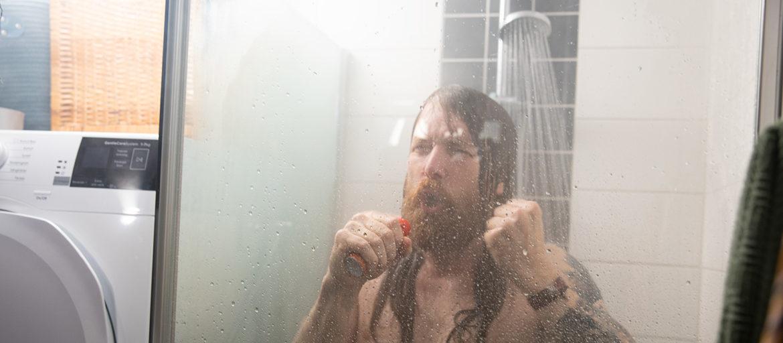 En man med långt hår står i duschen och sjunger