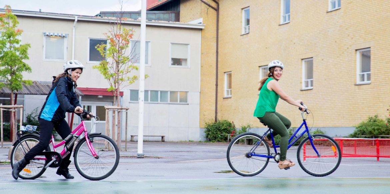 Två kvinnor som cyklar utanför en gul byggnad