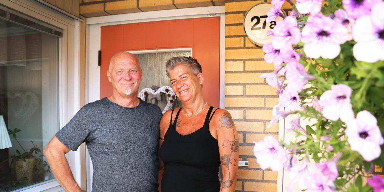 Ett par står bredvid varandra utanför sin dörr.
