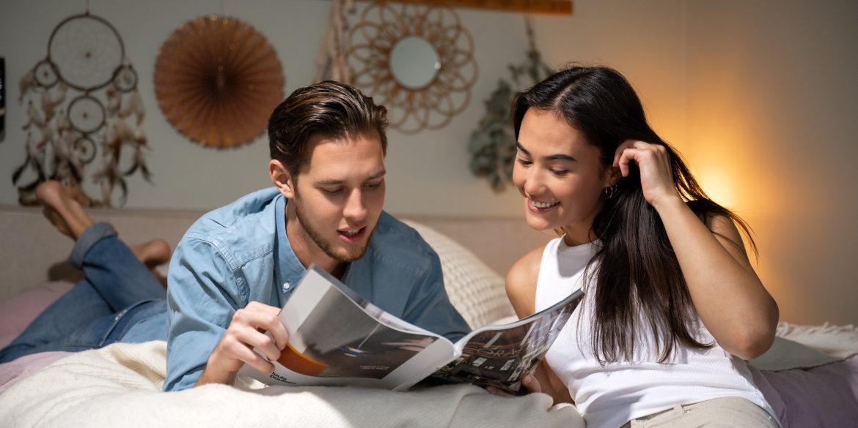 En kille och tjej ligger i sängen och läser en tidning
