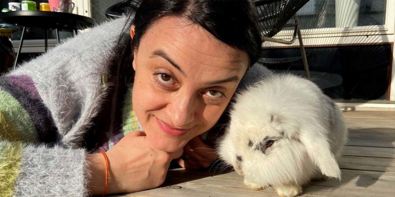 En kvinna myser med en kanin på terrassen
