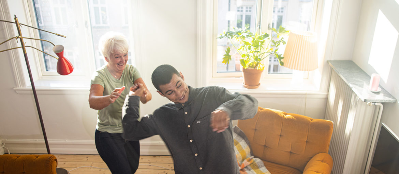 En son och mor som dansar i ett vardagsrum