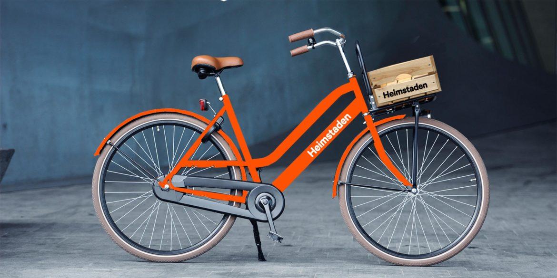 En orange cykel med en låda framtill som det står Heimstaden på