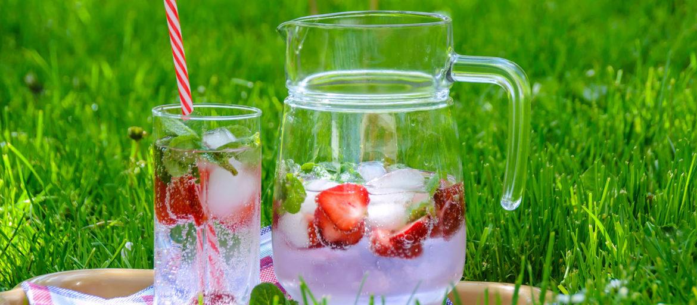 Ett glas och en kanna som står på en gräsmatta