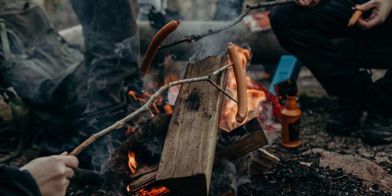 En öppen eld i skogen där några grillar korv på träspett