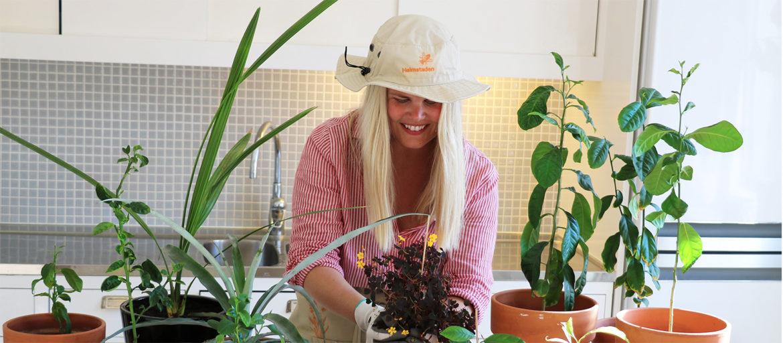 En ljushårig tjej står och planterar i sina krukor i köket