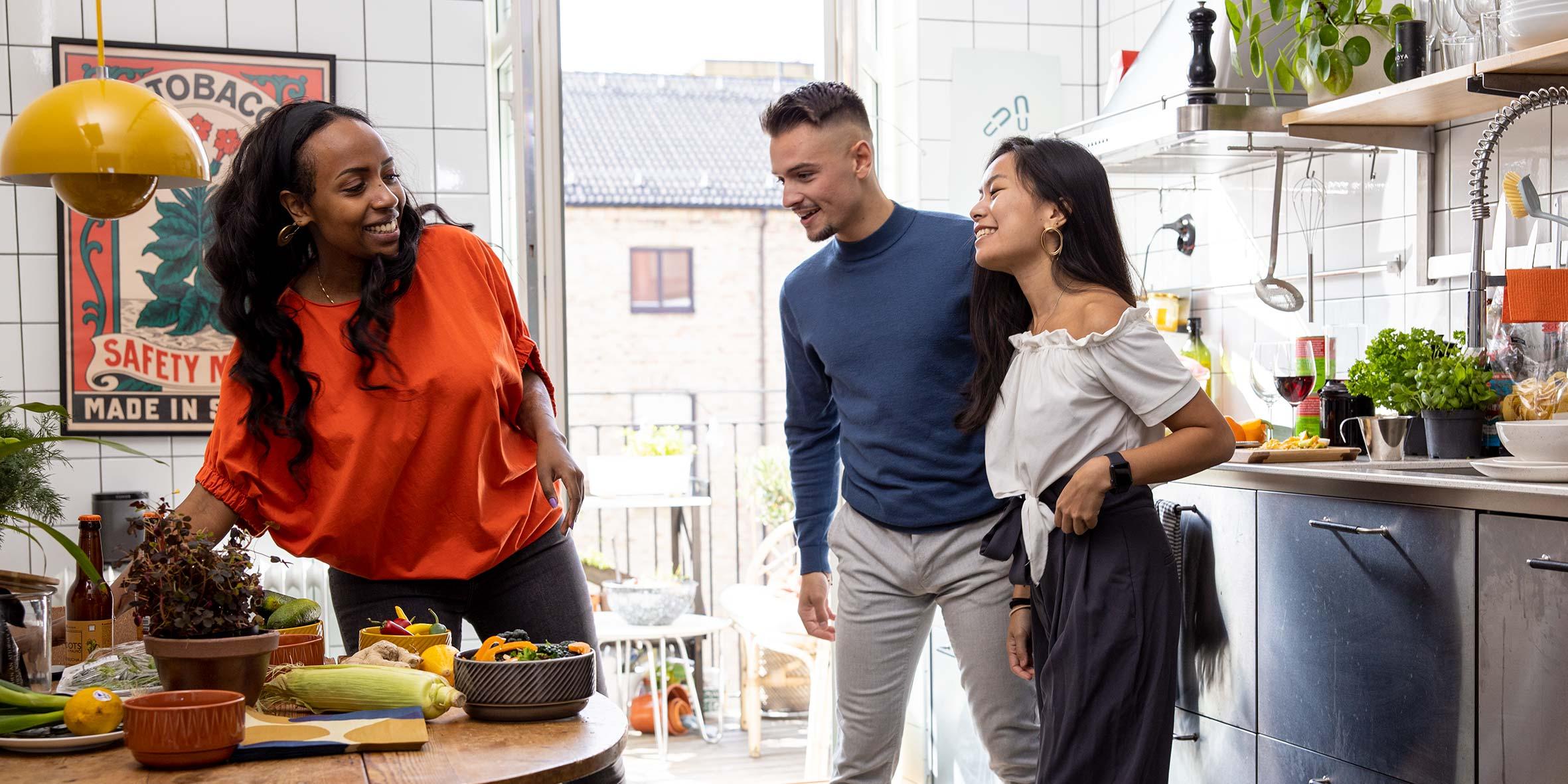 En kille och två tjejer står i ett kök och pratar