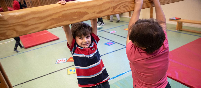 Ett barn i randig tröja håller i en träbalk i en gympasal