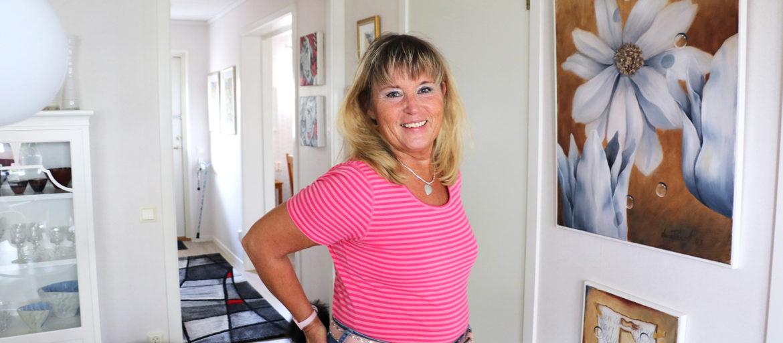En ljushårig kvinna i rosa t-shirt står i hennes hall