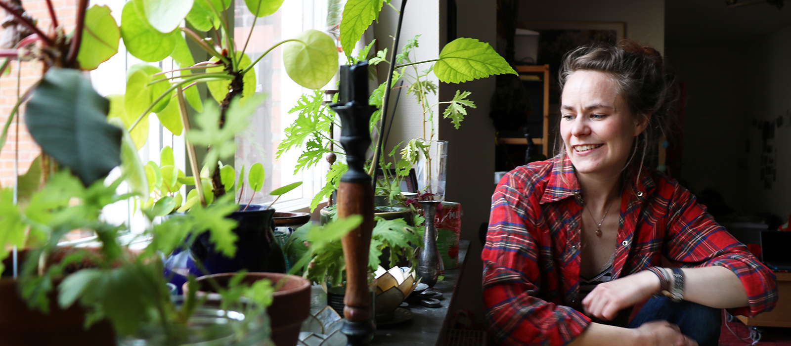 En mörkhårig tjej sitter och tittar på sina gröna växter i fönstret