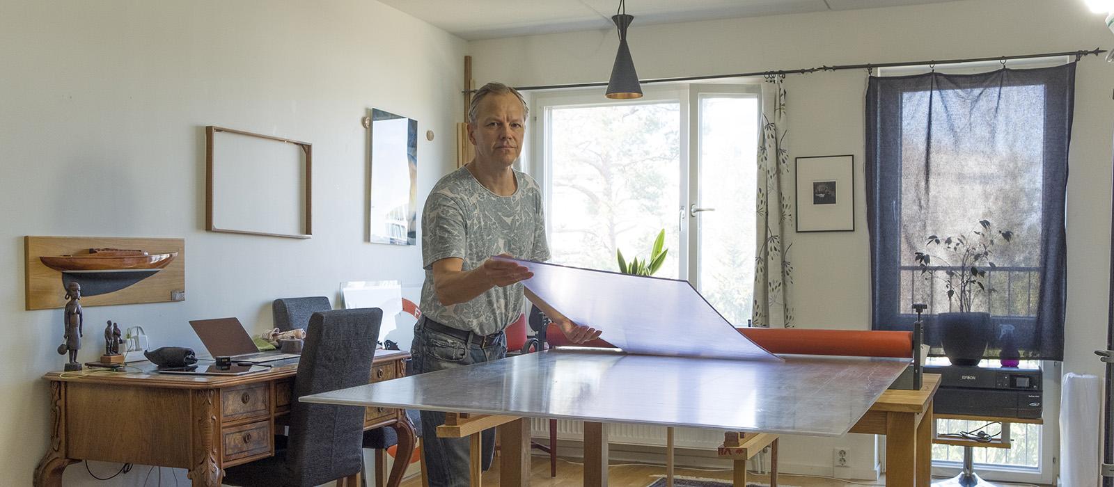 En man i grå t-shirt står vid ett arbetsbord med plexiglasskivor