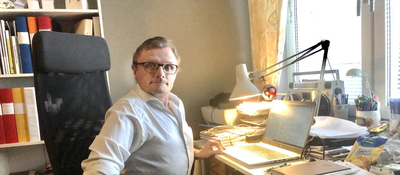 En man i vit skjorta sitter vid sitt skrivbord i hemmet