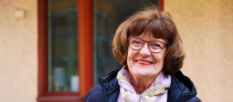 En brunhårig kvinna med röda glasögon och en mönstrad halsduk ler mot kameran