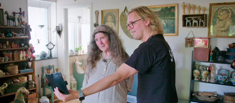 En kvinna och man står i ett vardagsrum fullt med massa antika saker