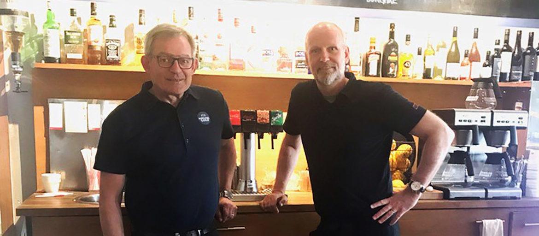 Två män i svarta pikétröjor står framför en bar