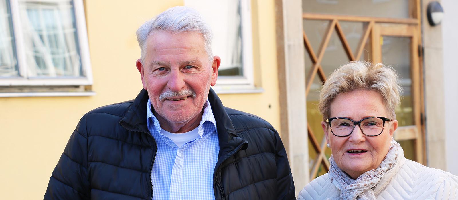 En man med blå skjorta och svart jacka och en kvinna med ljus jacka står bredvid varandra