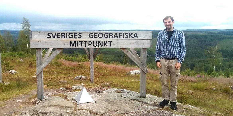 En man står på ett berg framför en skylt som det står Sveriges geografiska mittpunkt på