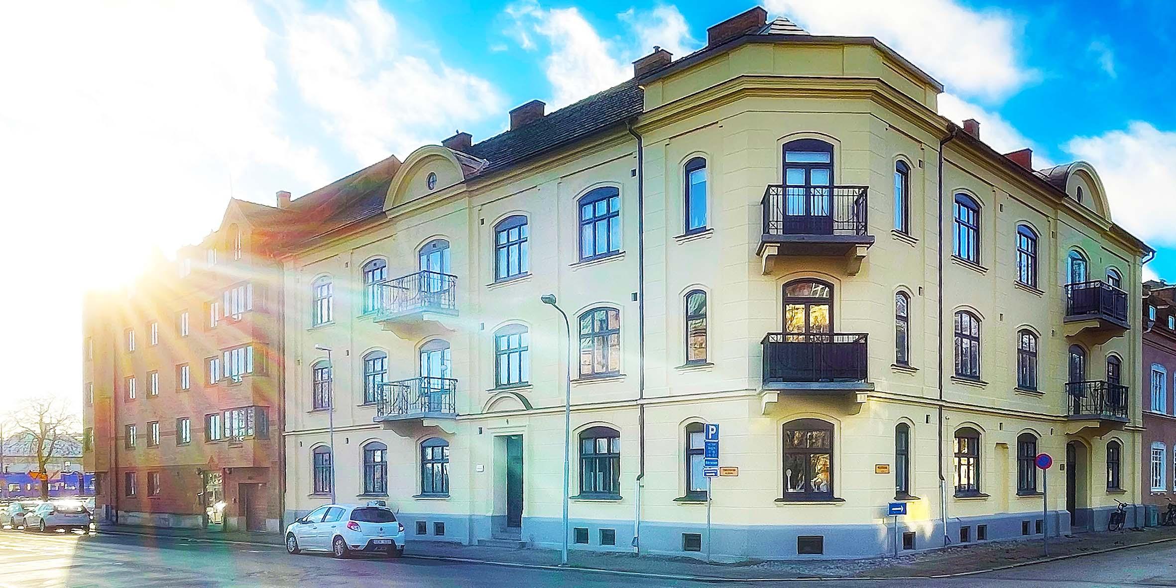 En ljusgul fasad med vackra gamla smidesbalkonger