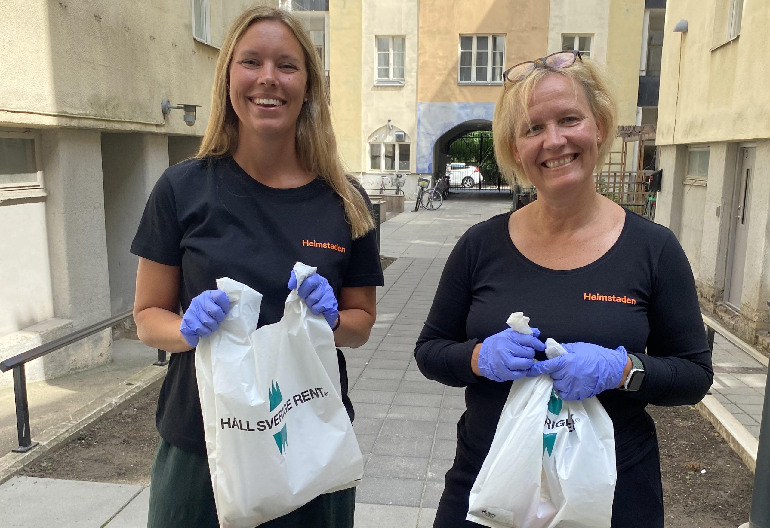 Två kvinnor med svarta tröjor som det står Heimstaden på, står med en påse i handen som det står Håll Sverige rent på.