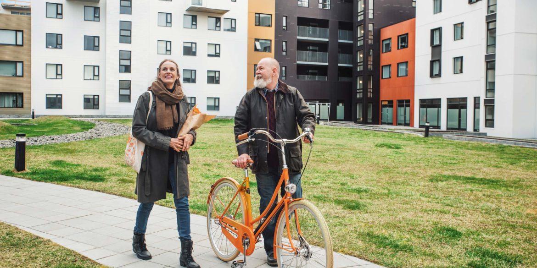 En kvinna och man går med en cykel i ett bostadsområde
